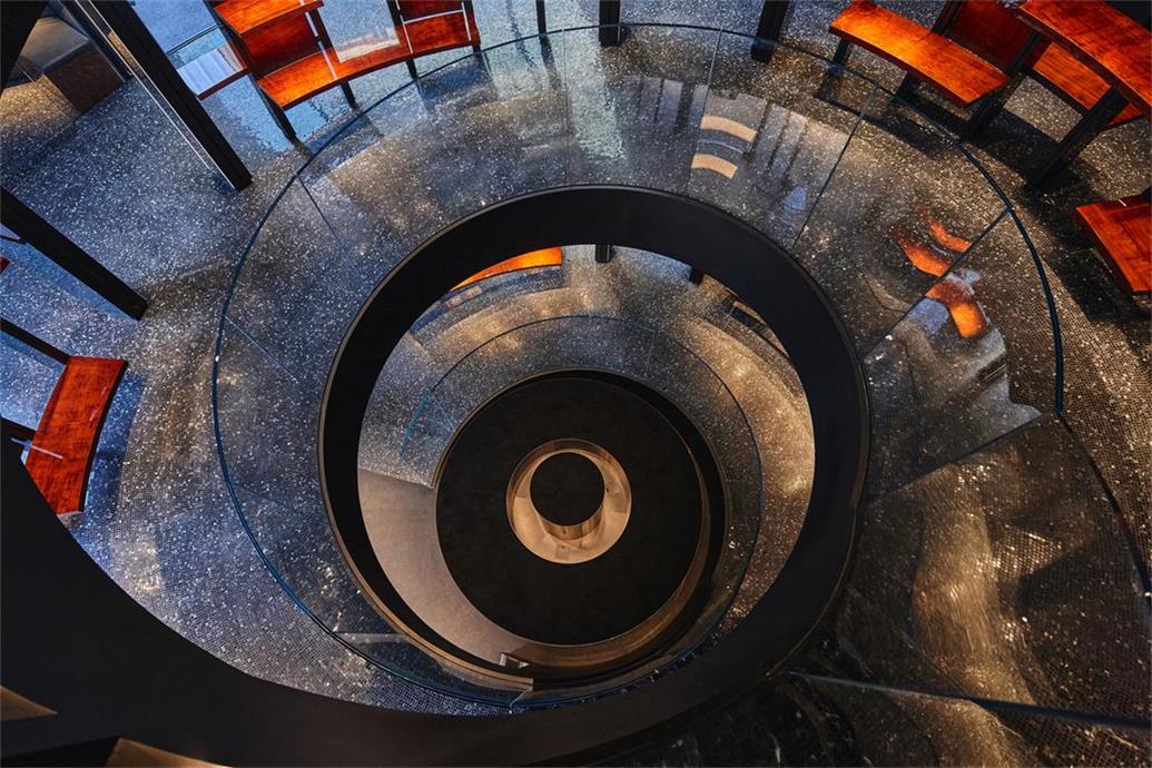 从奢侈品店顶层栏杆处望向一层楼梯间的场景