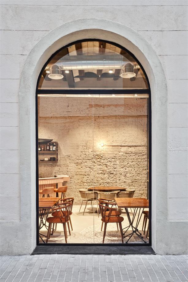 通过小型餐吧外立面窗户望向室内场景