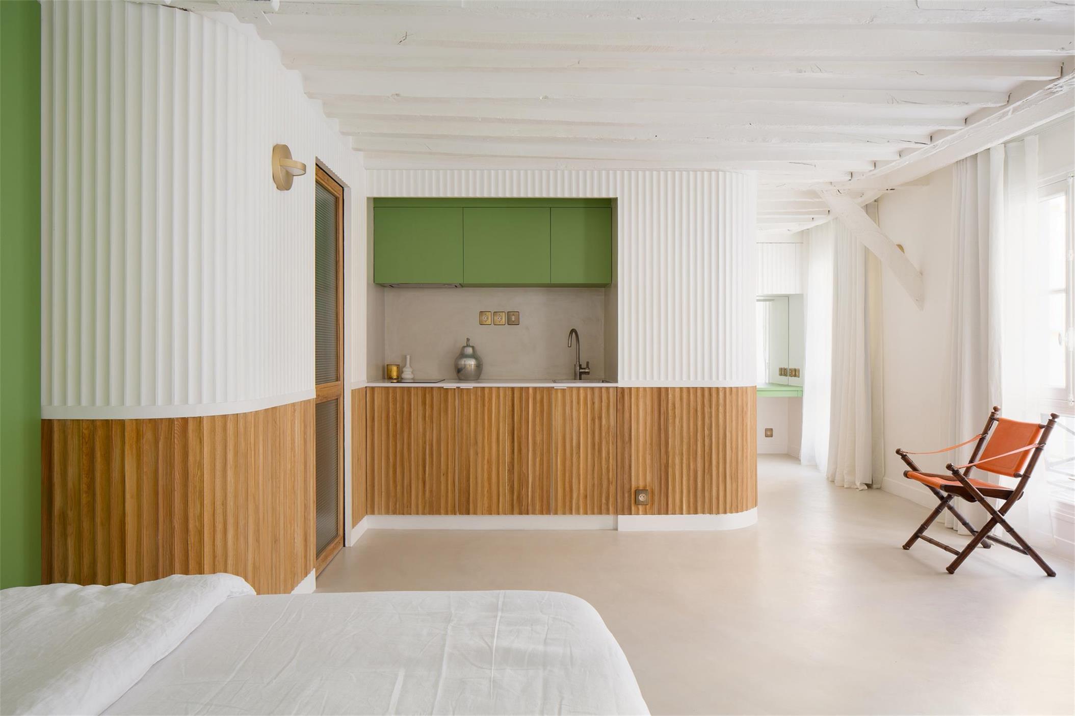从小型公寓睡眠区望向开放式厨房的场景